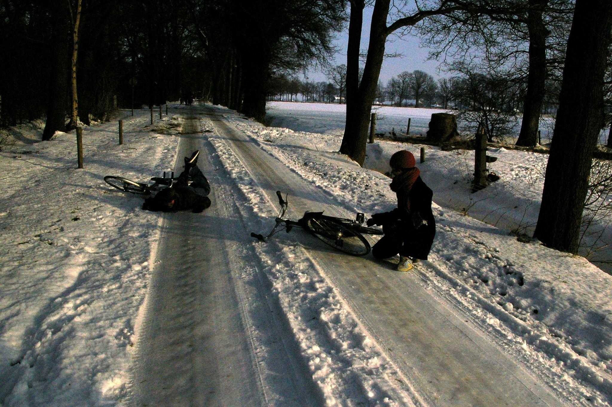 Fietsers vallen door de gladheid van de sneeuw